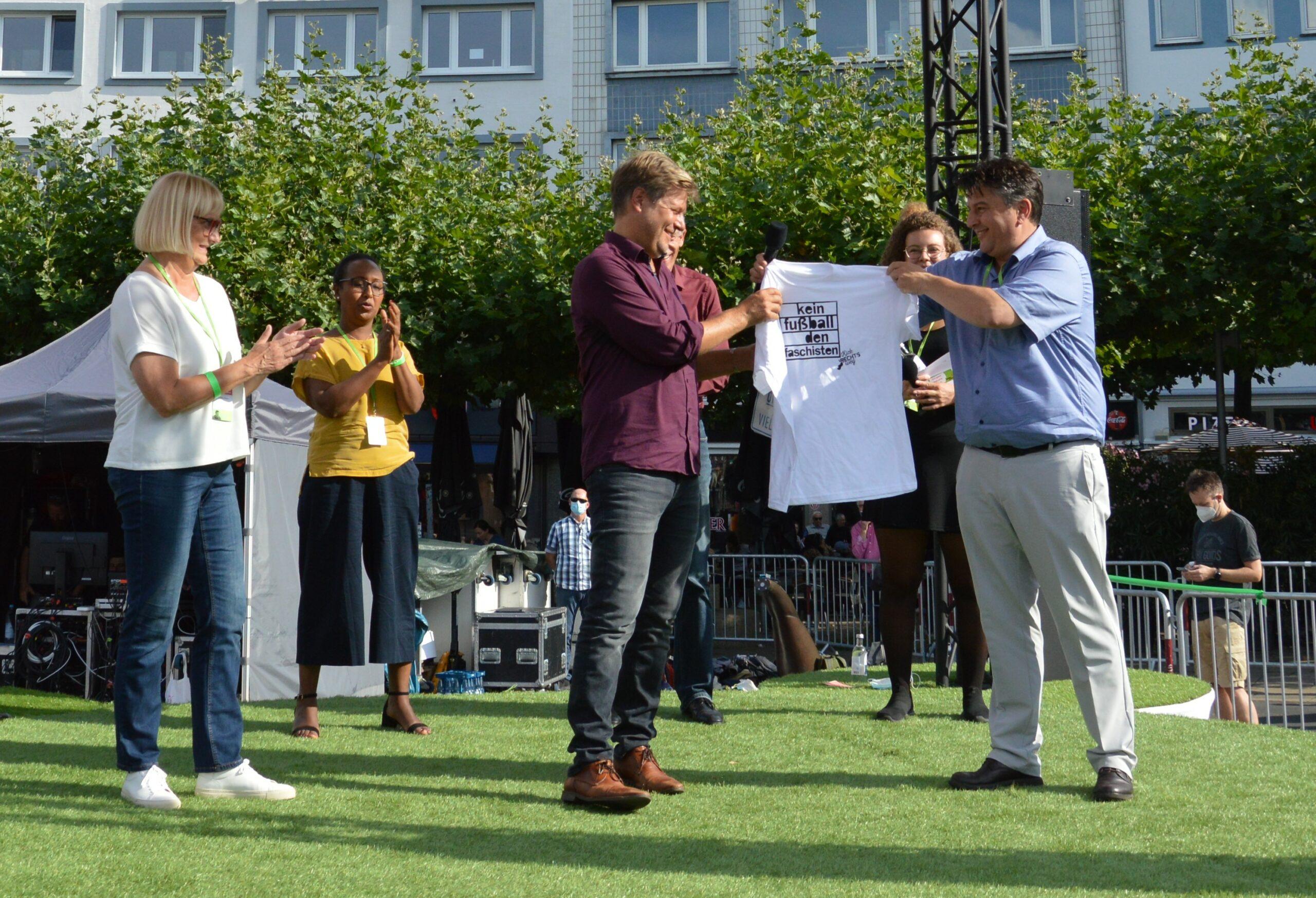 """Boris Mijatovic überreicht Robert Habeck ein weißes T-Shirt mit der Aufschrift """"Kein Fußball den Faschisten"""" von Kick rechts weg. Dr. Bettina Hoffmann, Awet Tesfaiesus, Dr. Peter Koswig und Sophie Eltzner applaudieren."""